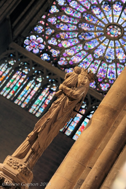 A statue of the Virgin Mary holding the Christ child in Notre-Dame-de-Paris Cathedral